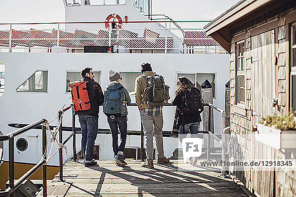 Four adult friends waiting with backpacks for ferry  Portland  Maine  USA