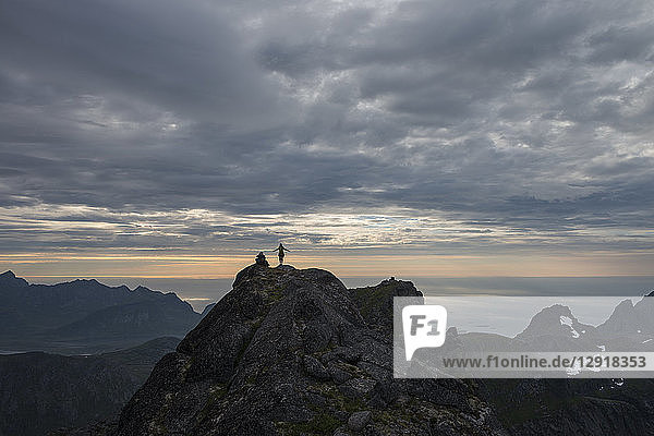 Distant view of female hiker on summit of Stjerntind at sunset  highest peak of Flakstad community  Flakstadoya  Lofoten Islands  Norway