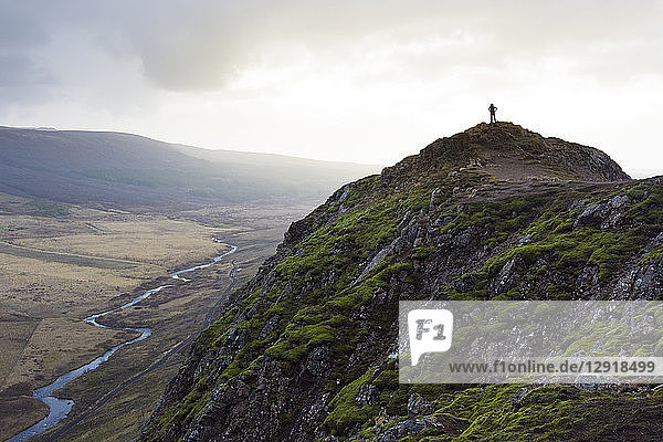 Silhouette of female hiker standing on top of mossy mountain overlooking river  Geysir  Iceland