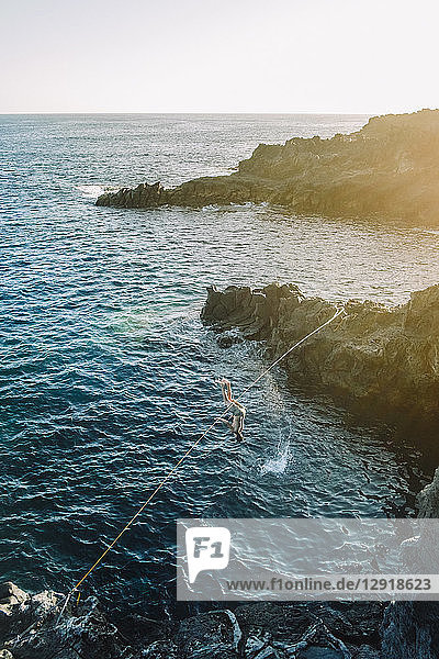 Young man falling off tightrope while trying to cross coastal water ¬ÝTenerife  Canary Islands  Spain
