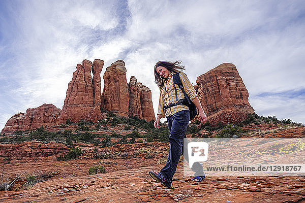 Female hiker walking down rocks at Cathedral Rock  Arizona  USA
