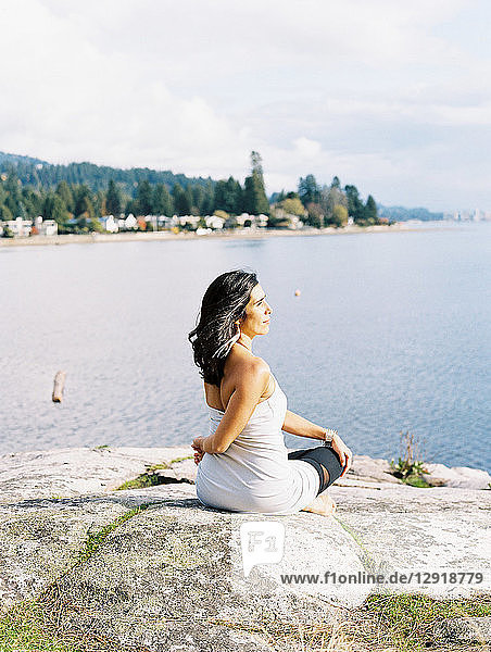 Woman with black hair sitting and turning torso while doing yoga on seashore