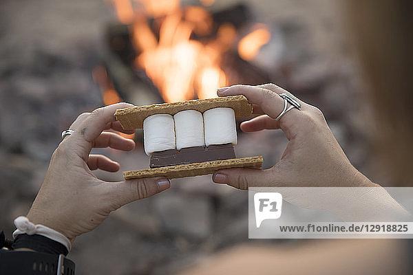 A woman's hands prepares s'mores at a campfire.