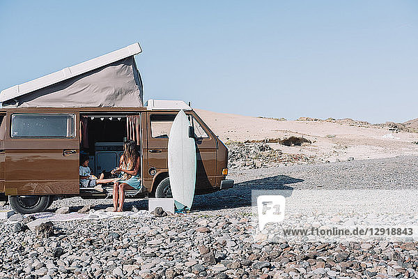 Pulled back view of young family sitting by vintage camper van on cobblestone beach at daytime  Tenerife  Canary Islands  Spain
