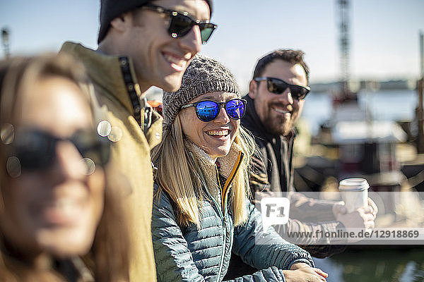 Portrait of young woman wearing sunglasses laughing while waiting with friends at harbor  Portland  Maine  USA