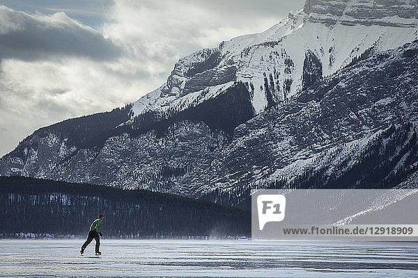Side view of man ice skating on frozen Lake Minnewanka in winter  Banff National Park  Alberta  Canada
