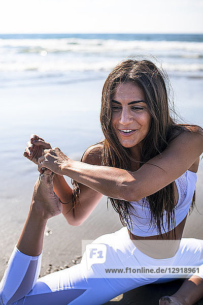 Young woman with black hair doing yoga on beach