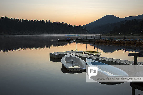 Tranquil scene with rowboats and jetty on shore of Evergreen Lake at sunrise  Colorado  USA