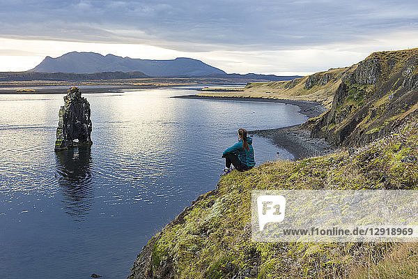 Female hiker sitting at edge of coastal cliff and looking at rock formation  Hvitserkur  Iceland