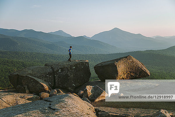 Distant view of woman standing on boulder while hiking  Pitchoff Mountain  Adirondack Mountains  New York State  USA