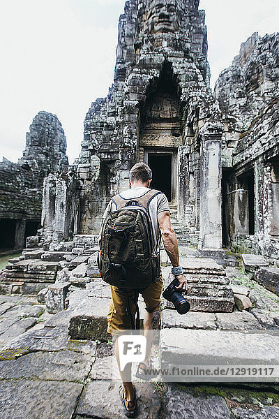Rear view shot of a single tourist holding a camera exploring ancient Cambodian temple  Siem†Reap Province  Cambodia