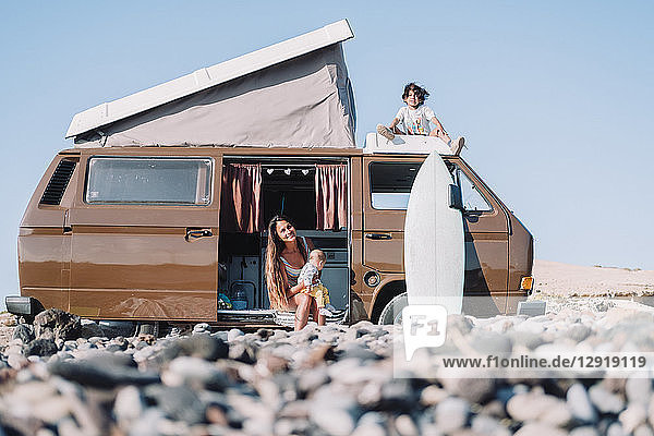 Pulled back view of young family sitting by vintage camper van on cobblestone beach  Tenerife  Canary Islands  Spain