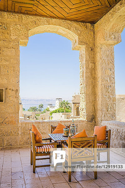 Table and chairs on covered terrace of Movenpick Dead Sea Spa and Resort with village in background  Madaba Governorate  Jordan