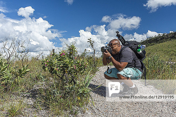Young adult photographer taking pictures of typical cerrado plants in Chapada dos Veadeiros  Goias  central Brazil