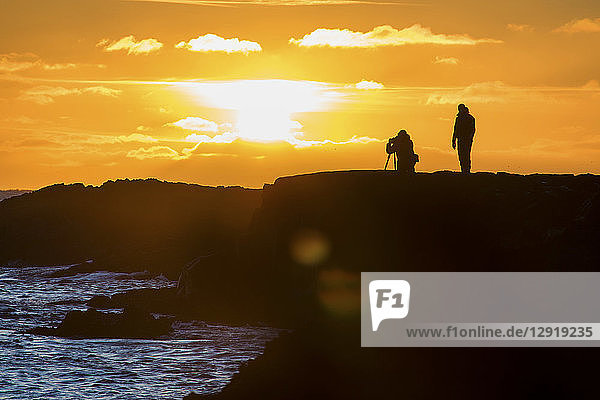 Silhouetted view of two photographers capturing setting sun on Reykjanes Southern Peninsula  Reykjanes  Iceland