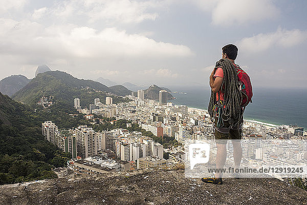 Male adult climber on rocky edge with a view to mountains and the city  Agulinha de Copacabana in Rio de Janeiro  Brazil
