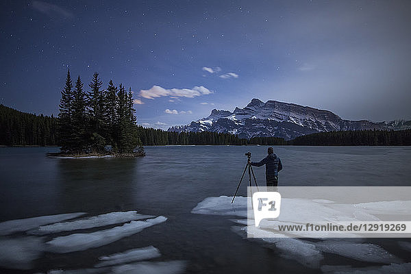 Photographer with camera on tripod standing on ice in Two Jack Lake at night  Banff National Park  Alberta  Canada