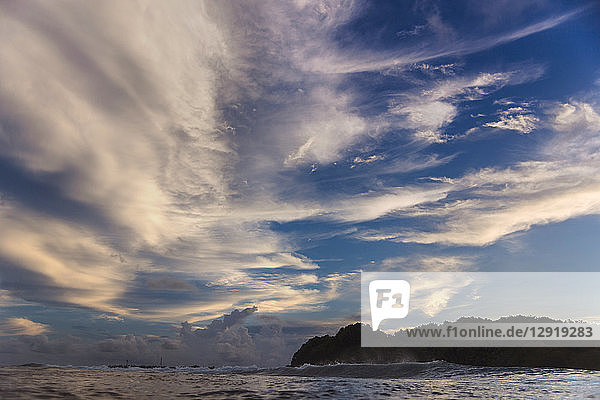 Large clouds over ocean and forested island at dawn  Male  Maldives