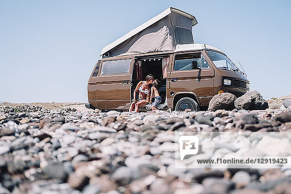Stones in front of pulled back view of mum and son kissing in vintage camper van  Tenerife  Canary Islands  Spain