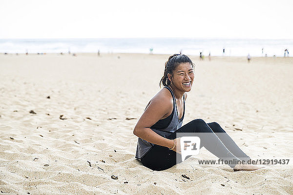 Happy female athlete sits on sandy beach at daytime  Oahu  Hawaii  USA