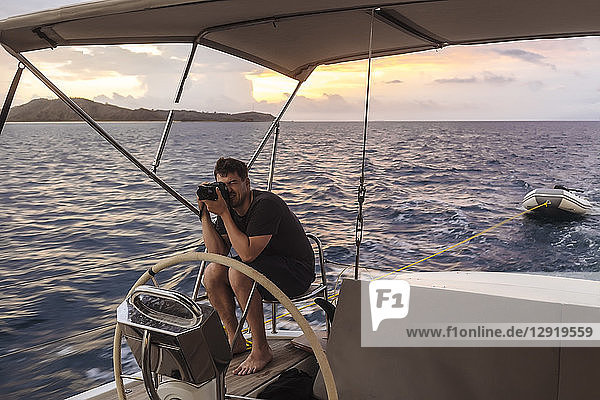 Full length shot of young man with camera on sailboat at sunset