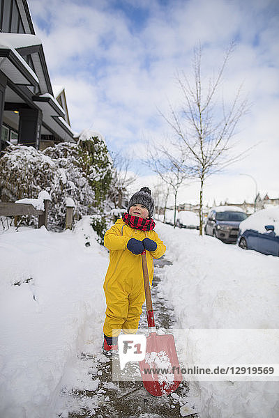 Front view shot of toddler shoveling snow in suburb