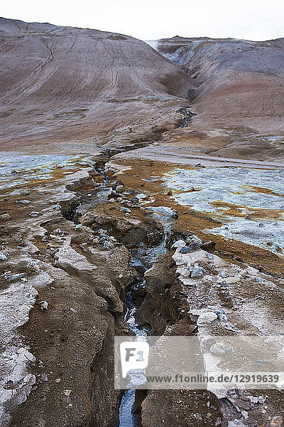 A cobalt coloured stream flows down from Namafjall mountain through the Hverarˆšˆ'ndor Hverir Geothermal Area  traversing brightly coloured minerals and soil at Namaskard Pass  North Iceland.