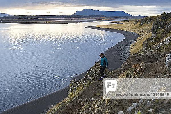 Female hiker descending coastal cliff and walking toward ocean coastline  Hvitserkur  Iceland