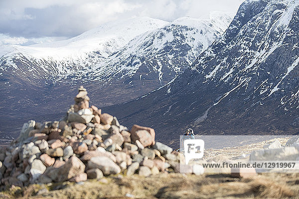 A cairn and a walker at the top of the Devils Staircase while hiking along the West Highland Way near Glencoe in the Scottish Highlands  Scotland  United Kingdom