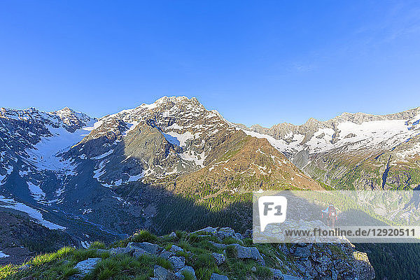 A hiker looks at Mount Disgrazia from above  Chiareggio valley  Valmalenco  Valtellina  Lombardy  Italy  Europe