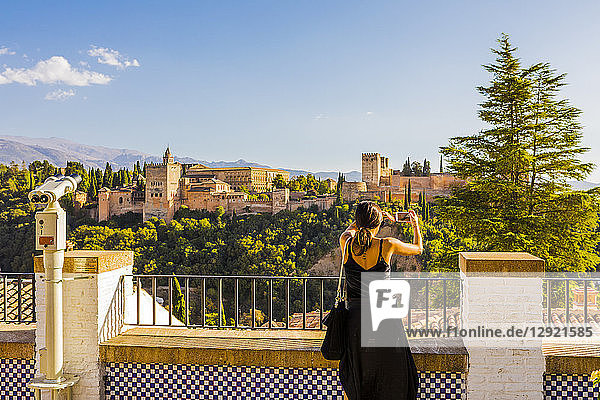Woman taking a photo of Alhambra and Sierra Nevada mountains  Granada  Andalucia  Spain  Europe