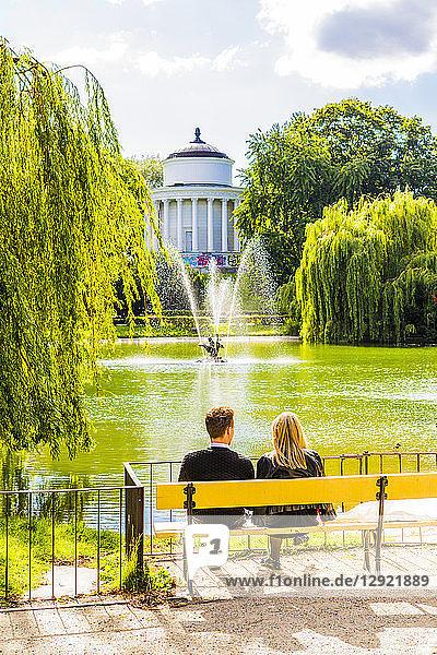 Couple sitting on a bench in Saxon Garden  Warsaw  Poland