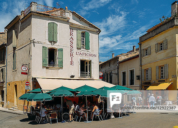Tourists sit at an outdoor terrace in the historic centre of Arles  Bouches-du Rhone  Provence  France  Europe