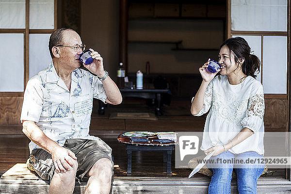 Japanischer Mann und Frau sitzen auf dem Boden auf der Veranda eines traditionellen japanischen Hauses und trinken Tee.