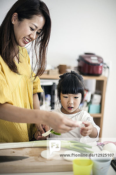 Japanese woman and young girl standing at a kitchen table  cutting leeks.
