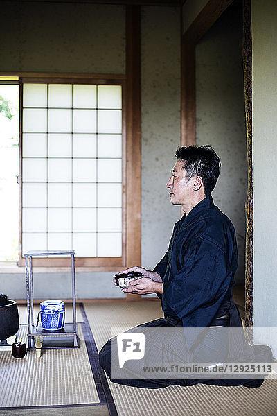 Japanischer Mann in traditionellem Kimono  auf dem Boden kniend  eine Teeschale haltend  während der Teezeremonie.