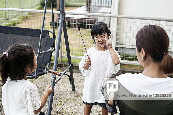 Two Japanese girls holding sausages on skewers and woman in a backyard.