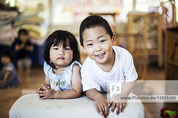 Smiling boy and girl in a Japanese preschool  looking at camera.