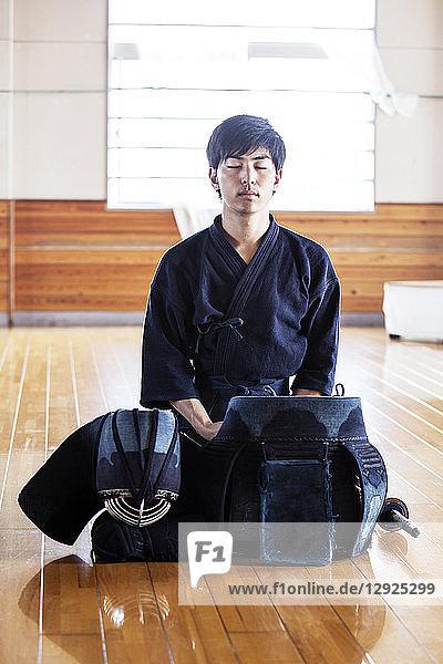 Male Japanese Kendo fighter kneeling on wooden floor  meditating.