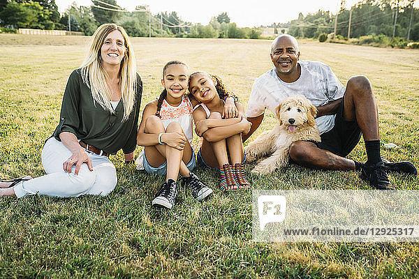 Porträt einer gemischtrassigen Familie im Feld mit Labradoodle-Welpe