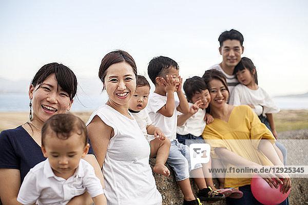 Gruppenporträt japanischer Familien mit kleinen Kindern auf einer Promenade am Meer  die in die Kamera lächeln.