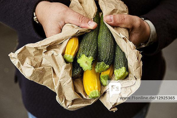 Eine Frau streckt ihre Hände aus und hält einen Strauß frisch gepflückter gelber und grüner Zucchini.