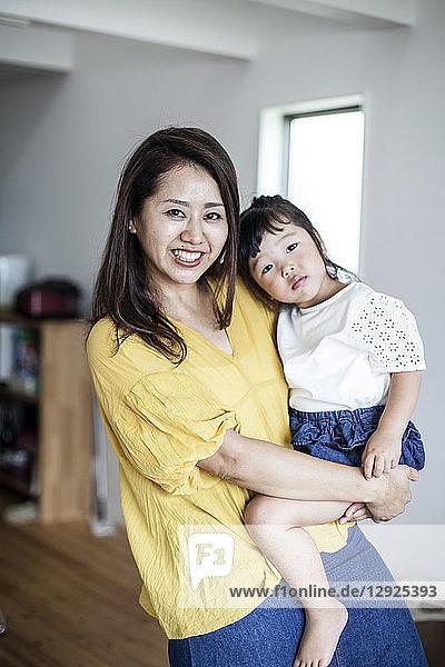 Porträt einer Japanerin  die in einem Wohnzimmer steht und ein junges Mädchen trägt  das in die Kamera lächelt.