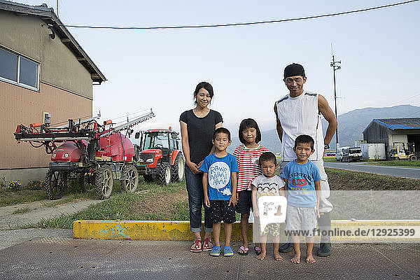 Portrait of Japanese farmer  his wife and four children standing in their yard.