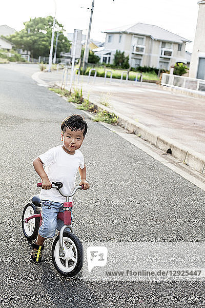 Portrait of Japanese boy playing on street with a bicycle  looking at camera.