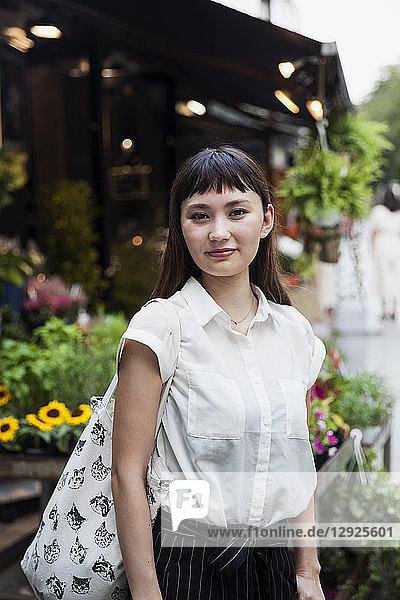 Japanerin mit langen braunen Haaren und weißer  kurzärmeliger Bluse  steht in einer Straße und lächelt in die Kamera.