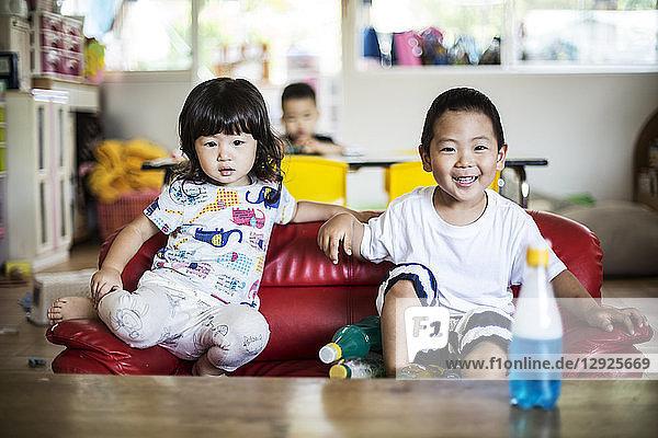 Lächelnder Junge und lächelndes Mädchen sitzen auf einem roten Sofa in einer japanischen Vorschule.