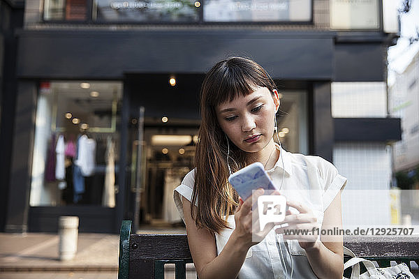 Japanese woman with long brown hair wearing white short-sleeved blouse standing in a street  looking at mobile phone.