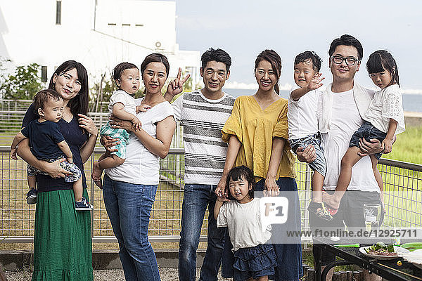 Gruppenporträt japanischer Familien mit kleinen Kindern  die in einem Hintergarten stehen und in die Kamera lächeln.