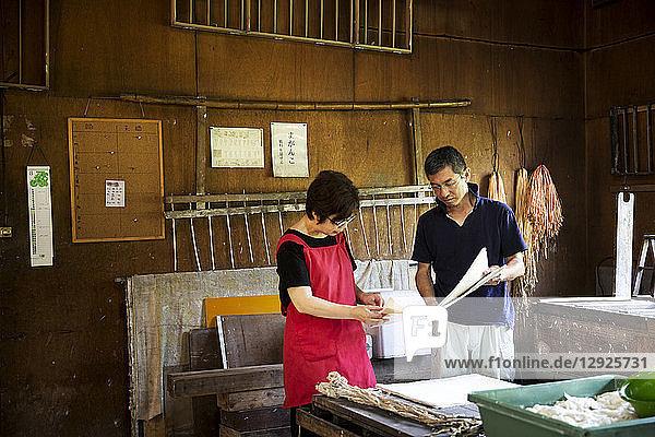 Japanischer Mann und Frau  Handwerker  die in einer traditionellen Werkstatt Washi-Papier herstellen.